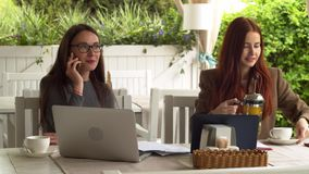 Brunette in big glasses talks on her phone discussing new interview for a lob at the cafe slow motion