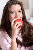 Brunette biting an apple Stock Photo
