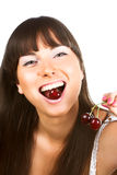 Brunette biting cherries Royalty Free Stock Photography