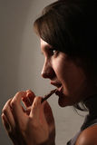 Brunette biting chocolate Stock Images