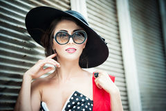 Brunette with black hat, red scarf and sunglasses posing outdoor. Attractive brunette girl with black hat, red scarf and sunglasses posing outdoor. Beautiful Stock Photo