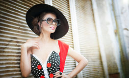 Brunette with black hat, red scarf and sunglasses posing outdoor. Attractive brunette girl with black hat, red scarf and sunglasses posing outdoor. Beautiful Stock Photography