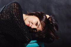 Brunette in a black sweatshirt on a black background. royalty free stock photography