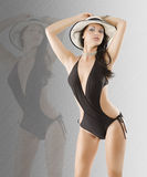 Brunette in black swimsuit. Cute and stunning brunette woman in black swimsuit and wet hair wearing an hat Royalty Free Stock Photography