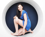 Brunette in blauwe kledingszitting in een cirkel stock foto