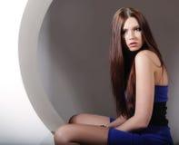 Brunette in blauwe kledingszitting in een cirkel Stock Afbeeldingen