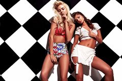 Brunette and blond models in rnb style clothes posing near chess wall. Fashion beautiful young brunette and blond models in rnb style clothes with pink colorful stock photo