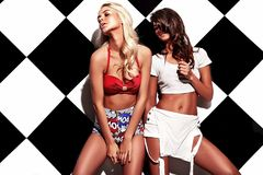 Brunette and blond models in rnb style clothes posing near chess wall Stock Images