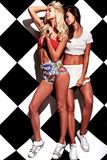 Brunette and blond models in rnb style clothes posing near chess wall Stock Image