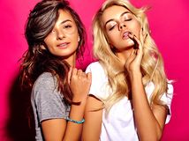 Brunette and blond models in summer casual clothes on colorful pink background Stock Images