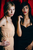Brunette and blond woman together friends, conflict of types on red curtain background, besties forever, lifestyle. Brunette and blond women together friends Stock Images