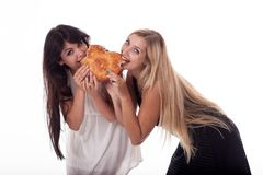 A brunette and blonde with long hair bite a bun in the shape of a heart. royalty free stock images