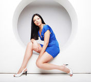 Brunette in blue dress sitting in a circle Stock Photography