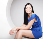 Brunette in blue dress sitting in a circle Royalty Free Stock Photo