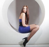 Brunette in blue dress sitting in a circle Stock Image