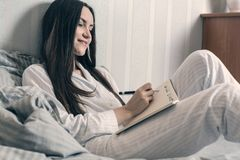 Brunette in blue pajamas lies in bed in the morning and makes a wish list.  stock photo