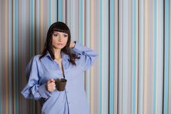 Brunette in a blue shirt holding a coffee cup Stock Photos