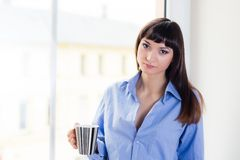 Brunette in a blue shirt holding a cup Royalty Free Stock Photography