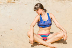 Brunette in a blue shirt relaxing in lotus pose Royalty Free Stock Photo