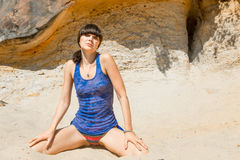 Brunette in a blue shirt and swimming trunks. Sitting on the sand Royalty Free Stock Photo