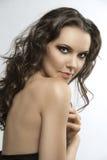 Brunette bonito com cabelo curly com mão no h Foto de Stock