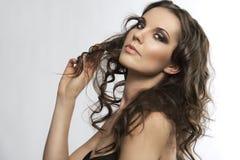 Brunette bonito con el pelo rizado con la mano en el h Foto de archivo libre de regalías