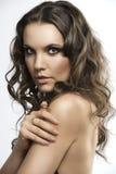 Brunette bonito con el pelo rizado con la mano en el h Fotos de archivo libres de regalías