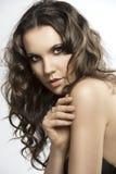 Brunette bonito con el pelo rizado con la mano en el h Imagenes de archivo