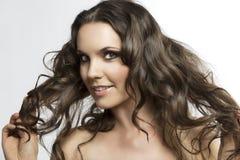 Brunette bonito con el pelo rizado con la mano en el h Imágenes de archivo libres de regalías