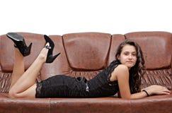 Brunette bonito en la alineada negra que pone el sofá Imágenes de archivo libres de regalías
