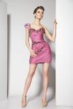 Brunette bonito novo no vestido cor-de-rosa no branco Imagens de Stock Royalty Free