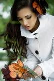 Brunette bonito que coleta as folhas imagem de stock royalty free