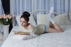 Brunette with a book in the room Stock Images