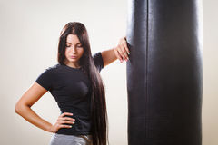 Brunette boxing girl and body hitting pear. Royalty Free Stock Photography