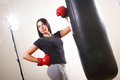 Brunette boxing girl in gloves and body hitting pear. Stock Photos