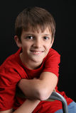 Brunette boy. Against a black background wearing red shirt stock images