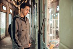 Brunette boy looking at shop at night stock images