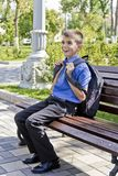 Brunette boy sitting on bench with school backpack. Brunette boy are sitting on the bench with school backpack royalty free stock images