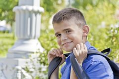 Cute brunette boy eleven years old. Brunette boy are smiling with school backpack stock image
