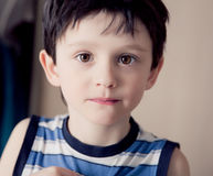 brunette boy wearing striped shirt indoor Royalty Free Stock Photos