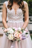Brunette bride in a beautiful pink wedding dress with embroidery on a corset holding a bouquet of peonies Royalty Free Stock Photos