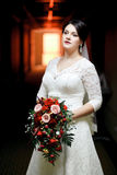 Brunette bride with bouquet standing in hotel hallway, tunnel light. Stock Image