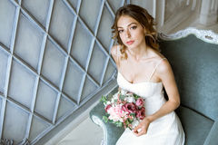 Brunette bride in fashion white wedding dress with makeup. Wedding day of bride in bridal gown. Beauty woman and bouquet. Fashion brunette model indoors Stock Photos