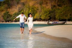Brunette bride and groom run in shallow sea Royalty Free Stock Photography