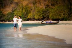 brunette bride and groom run in shallow sea Stock Images