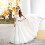 Brunette bride in long white dress posing at windy day at park Royalty Free Stock Image