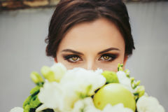 Brunette bride with magic green eyes looks over a green wedding. Bouqet royalty free stock image