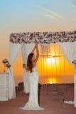 Brunette bride portrait. Wedding ceremony arch with flower arran Stock Photography
