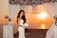 Brunette bride portrait. Wedding ceremony arch with flower arran Royalty Free Stock Photo