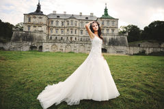 Brunette bride posing against castle in west Ukraine Royalty Free Stock Images